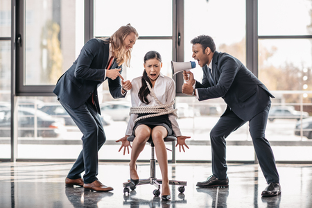 yelling asian businesswoman bound with rope on chair while businessmen screaming on her with megaphone