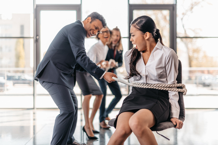 asian businesswoman bound with rope on chair and multicultural business team pulling her Imagens