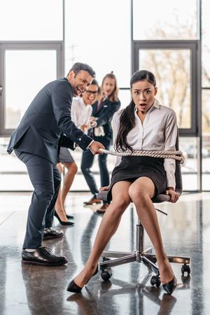 Empresaria asiática con la cuerda en la silla y el equipo de negocios multicultural tirando de ella, espíritu de equipo concepto de negocio Foto de archivo - 80859369