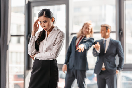 asian businesswoman standing in office, businessmen behind gesturing and laughing Stock Photo