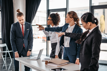Three angry young businesswomen pointing with fingers at upset businessman in office, business team meeting concept
