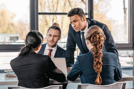 young coworkers in formalwear arguing at business meeting in office Stock Photo