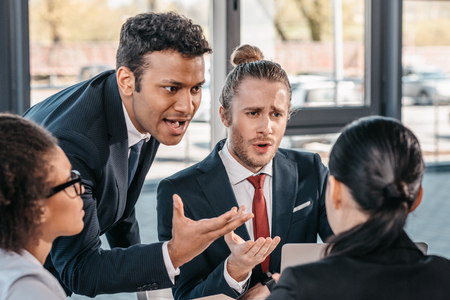 オフィス、ビジネスでの会議で議論して正装の若い感情的なビジネスマン チームにてミーティング 写真素材