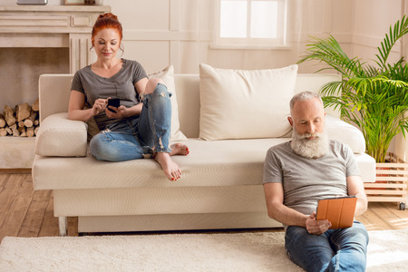 aged: husband using digital tablet and sitting on floor while wife using smartphone and sitting Stock Photo