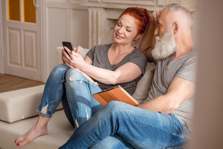 aged: Beautiful mature couple sitting together on couch and using smartphone and digital tablet Stock Photo