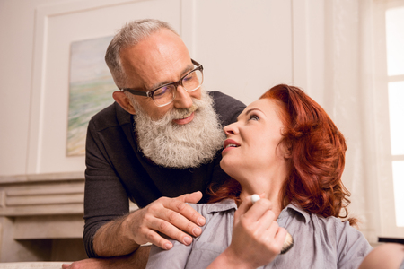 woman looking at husband near by while applying makeup at home