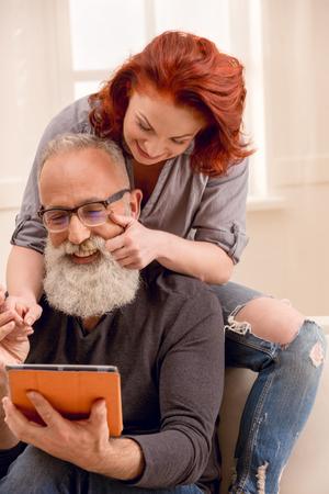 happy man using digital tablet with wife near by Stock fotó