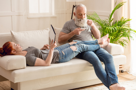 woman lying on sofa with digital tablet and bearded man drinking coffee at home Archivio Fotografico
