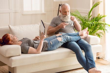 vrouw liggend op de bank met digitale tablet en bebaarde man drinken koffie thuis