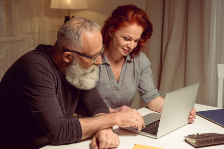 Porträt von Mann und Frau am Tisch sitzen und Laptop verwenden Standard-Bild - 80921053