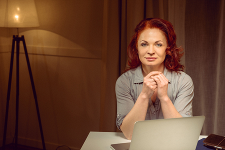 red hair woman sitting at table near laptop and looking at camera Stock Photo