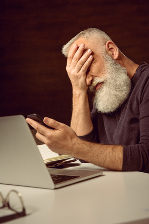 aged: haired man sitting at table and holding smartphone with facepalm at home
