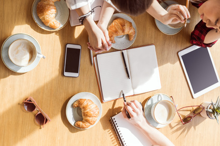 overhead view of young women sitting at coffee break with digital devices