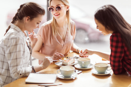 girls eating cake and drinking coffee at cafe, coffee break Stockfoto