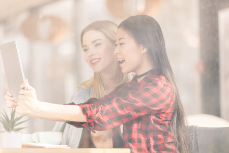 Smiling young women drinking coffee and using digital tablet together