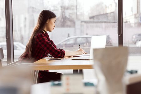 young woman using laptop and taking notes at coffee break