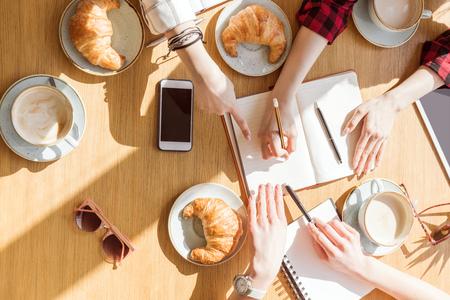 bovenaanzicht van jonge vrouwen zitten bij koffiepauze met digitale apparaten Stockfoto