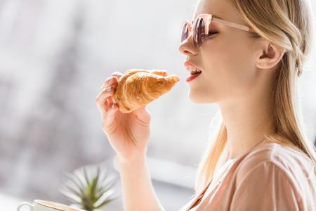 woman eating croissant while sitting in cafe, coffee break Stok Fotoğraf