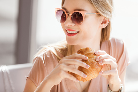 woman eating croissant while sitting in cafe, coffee break 스톡 콘텐츠