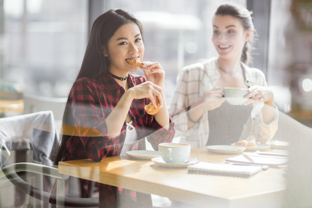girls eating croissants and drinking coffee at cafe, coffee break