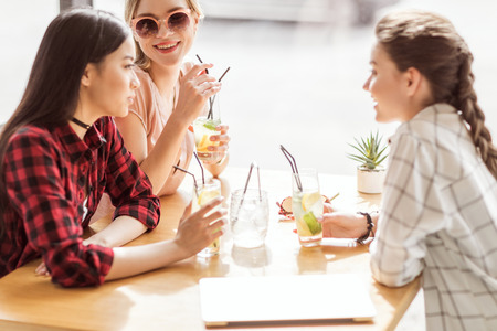 young girls drinking cocktails together while sitting at table in cafe
