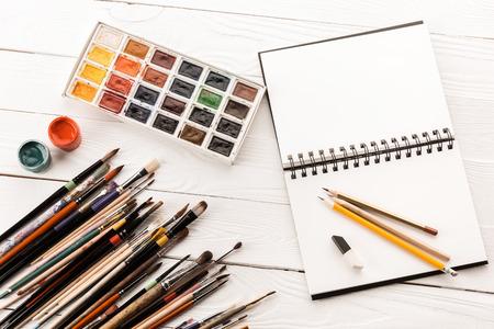様々 なペイント ブラシ、塗料、ノートブックを開く空白の平面図