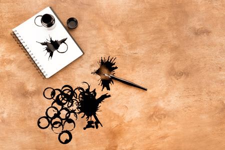 Tintenbehälter, Füllfederhalter, Notizbuch und Tinte spritzt auf Tabelle Standard-Bild - 80921999