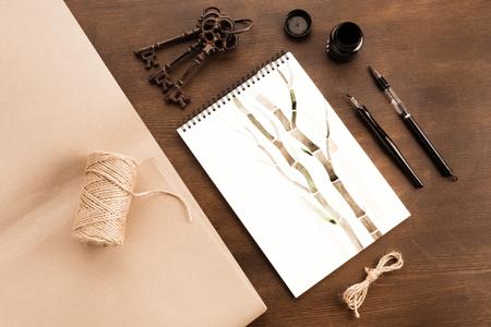 Bambuszeichnung im Album, Bürste, Füllfederhalter und Weinleseschlüssel auf Tabelle Standard-Bild - 80922000