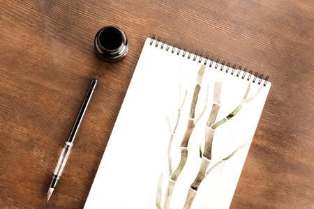 Bambuszeichnung im Album und Pinsel auf dem Tisch Standard-Bild - 80922001