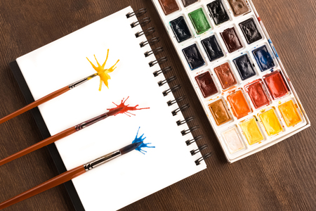 painting: Top view of brushes and paint splashes on paper with paints