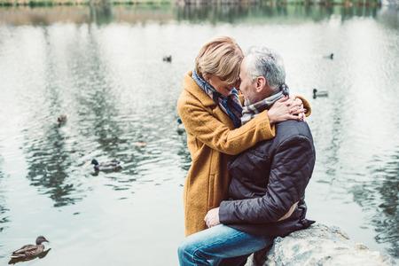 湖の近くを抱いて幸せな熟年カップル