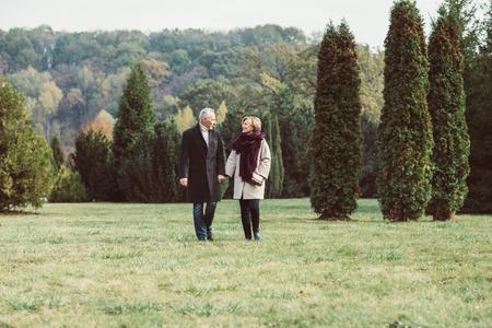 Mature couple walking in autumn park Stock Photo