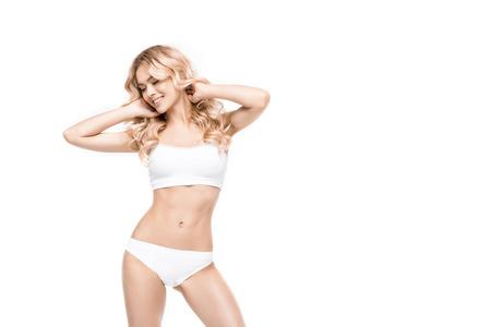 aantrekkelijke glimlachende vrouw die zich in wit ondergoed bevindt