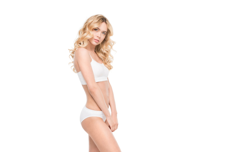 smiling woman standing in white underwear isolated on white in studio