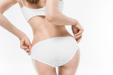 vrouw in wit ondergoed dat haar uiteinde toont dat op wit wordt geïsoleerd