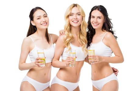 レモンの水のガラスを抱きしめると白い下着の女性