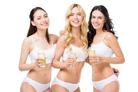 women in white underwear embracing and holding glasses of water with lemon