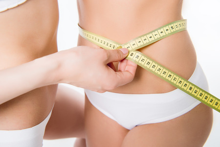 undergarment: girls using measuring tape to assess waist volume Stock Photo