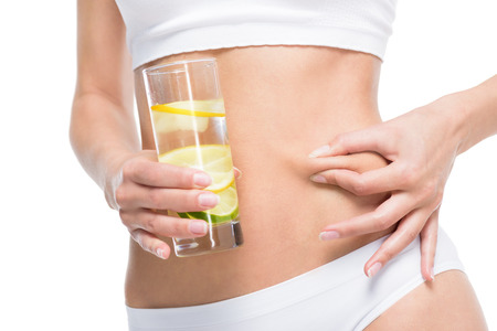 partial: partial view of woman holding glass of water and nipping stomach Stock Photo