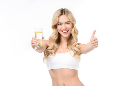 woman in white underwear holding glass of water with lemon and showing thumb up Imagens