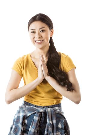 伝統的な挨拶のジェスチャーと若い笑顔のアジアの女の子