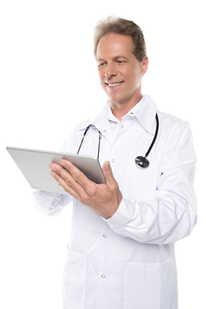 smiling middle aged doctor in white coat using digital tablet