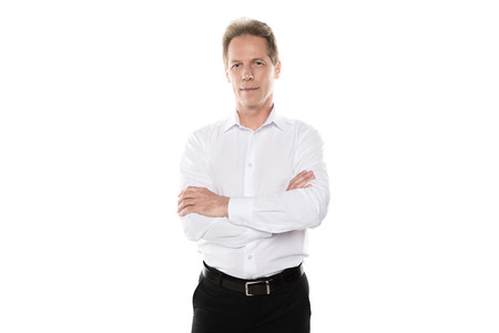 confident middle aged businessman in formal wear with crossed arms looking at camera Banco de Imagens