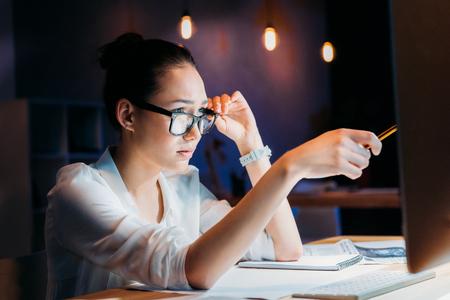 koncentrovaný: koncentrovaný asijské podnikatelka v brýlích ukazující na počítačový monitor