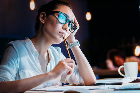 businesswoman in eyeglasses holding pencil and working late in office