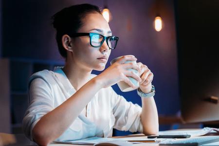 オフィスで残業しながらカップを保持している眼鏡の女性実業家