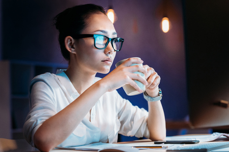 businesswoman in eyeglasses holding cup while working late in office