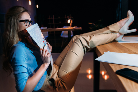 evening newspaper: businesswoman in eyeglasses holding newspaper while working late in office Stock Photo
