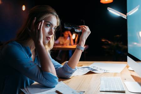 Junge Geschäftsfrau hält Brillen und Blick auf Desktop-Computer-Bildschirm Standard-Bild - 80980679