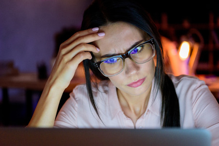 caucasian businesswoman looking on laptop in thoughtful pose Stock Photo
